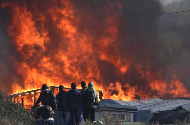 People watch as thick smoke and flames rise from amidst the tents in Calais on