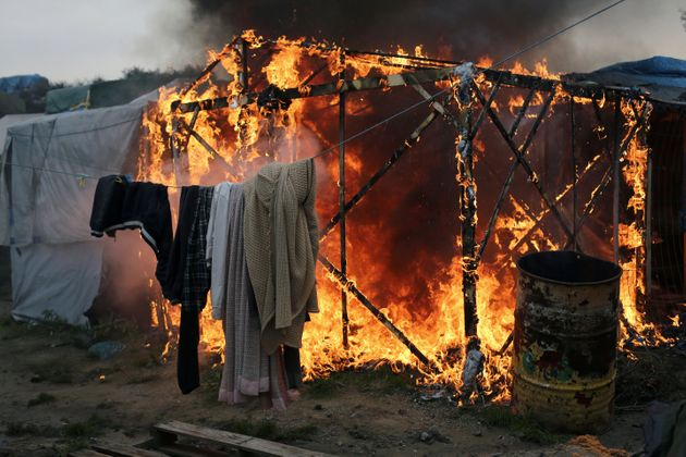 Washing still hangs on a line as a structure burns in the