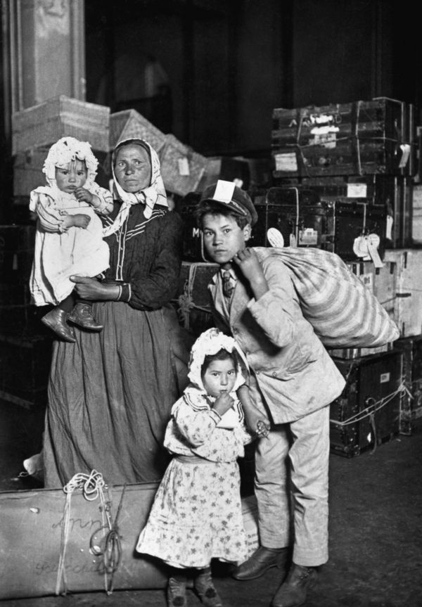 An Italian woman, Anna Schiacchitano, and her children, Paolo (eldest), Mary and Domenico (in Anna's arms), arrive at Ellis I