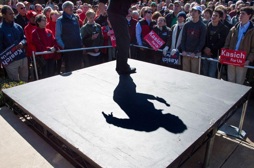Supporters listen as Republican presidential candidate John Kasich speaks outside Mutt's BBQ in Mauldin, South Carolina, on F