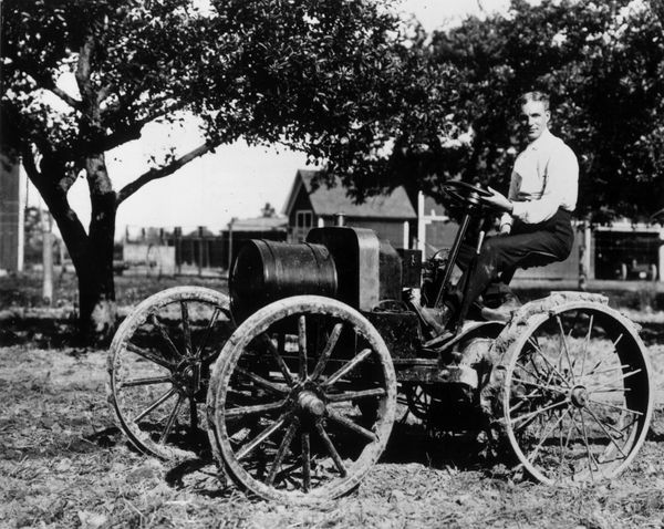 "American inventor and manufacturer Henry Ford drives an early tractor, which he called an ""automobile plow,"" powered by a 190"