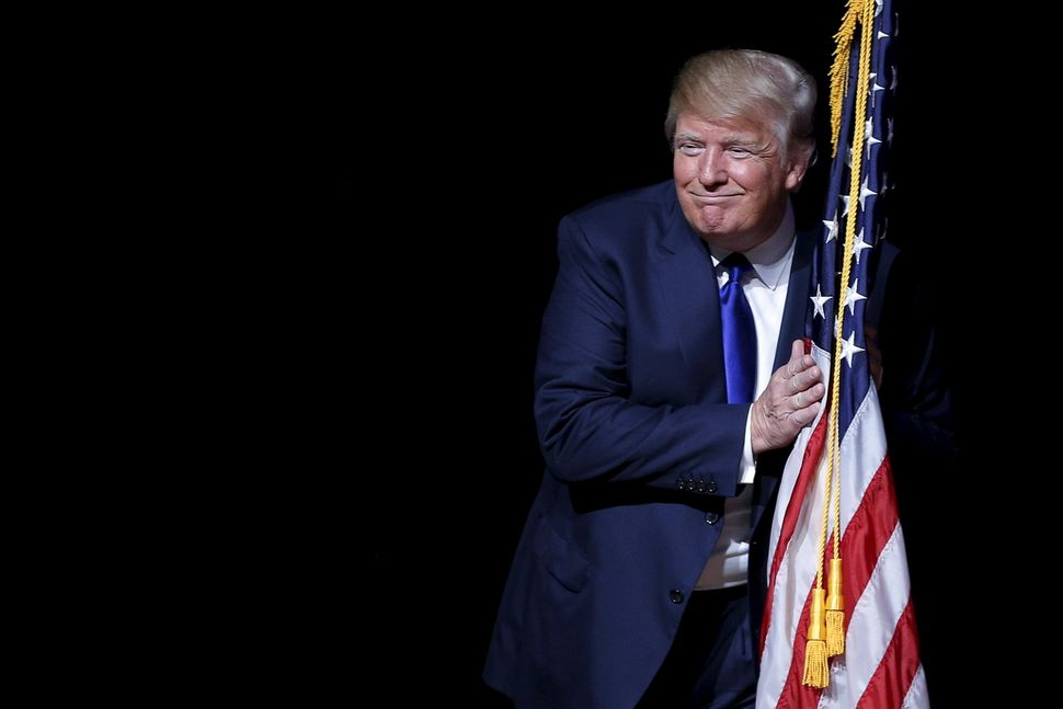 Trump hugs a U.S. flag as he takes the stage for a town hall meeting in Derry, New Hampshire, on Aug. 19, 2015.