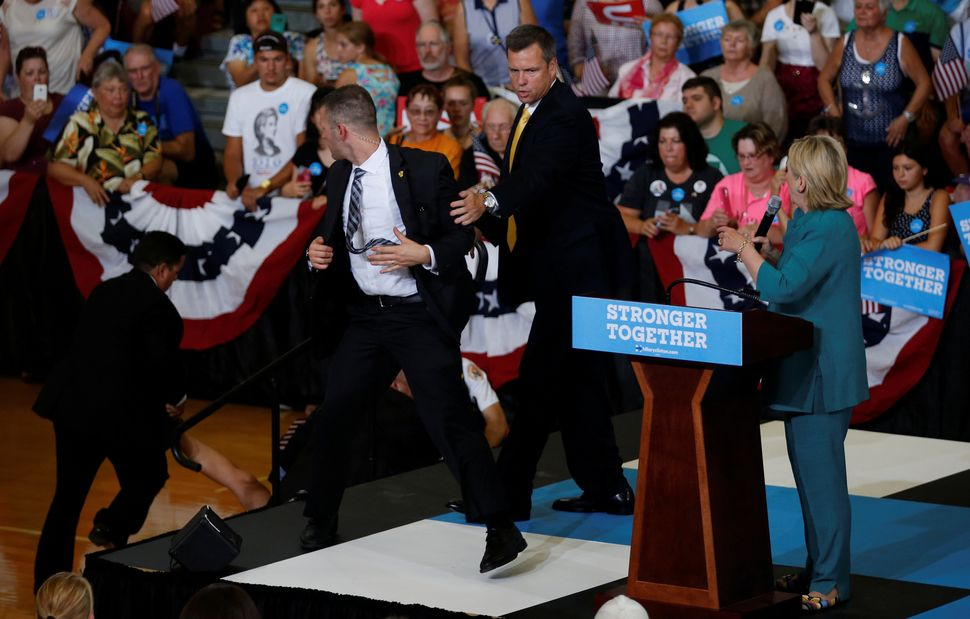 Secret Service officers handle the situation after a protester jumped into the buffer between the audience and Hillary Clinto