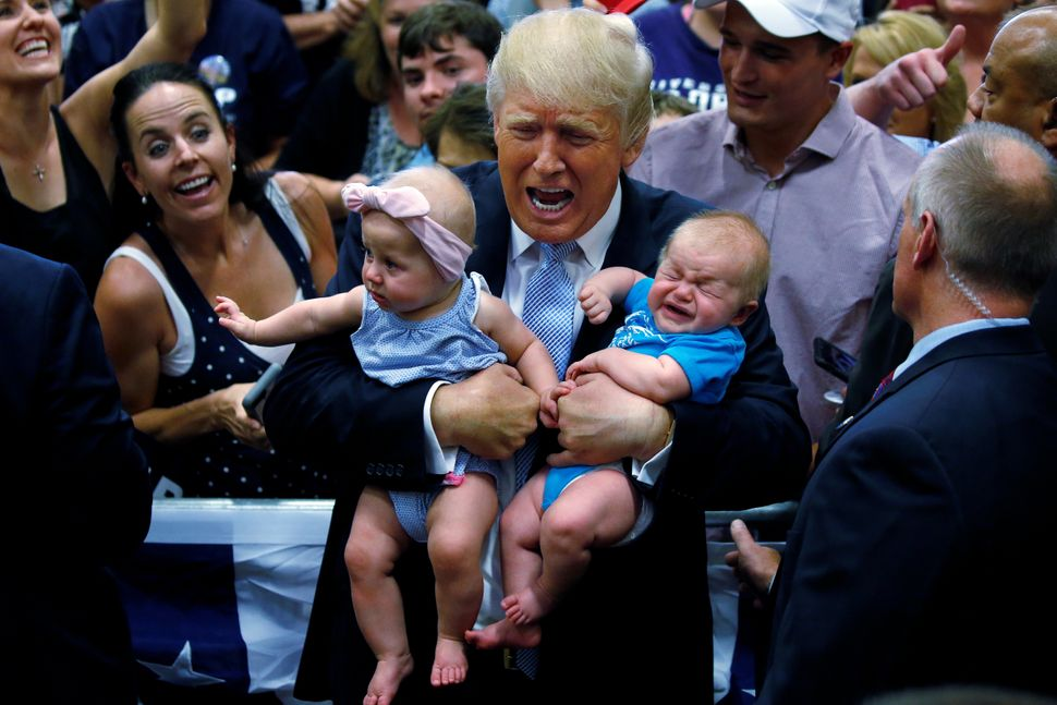 Republican nominee Donald Trump holds babies at a campaign rally in Colorado SpringsonJuly 29, 2016.