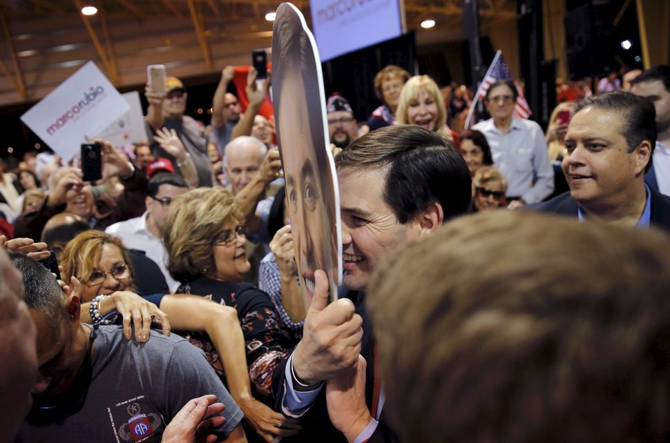 Republican candidate Sen. Marco Rubio holds up a cutout of his head as he greets supporters after speaking about the Super Tu
