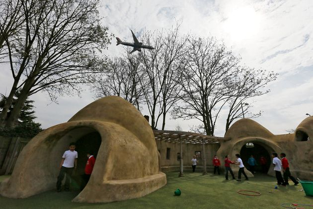 Students from Hounslow Heath Infants School play around one of four adobe huts designed to help minimise...