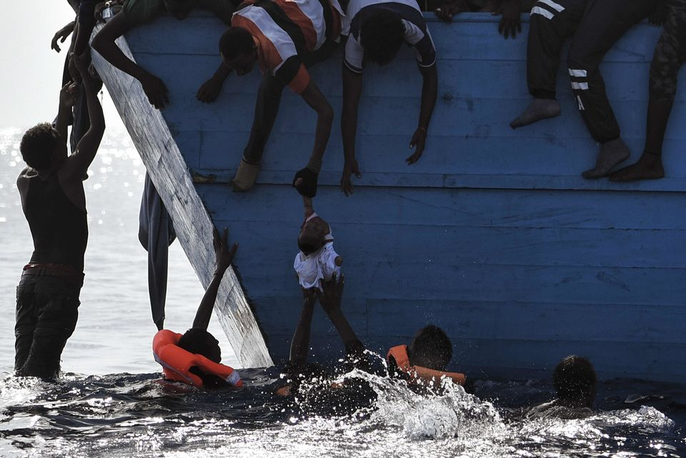TOPSHOT - Migrants try to pull a child out of the water as they wait to be rescued by members of Proactiva Open Arms NGO in t