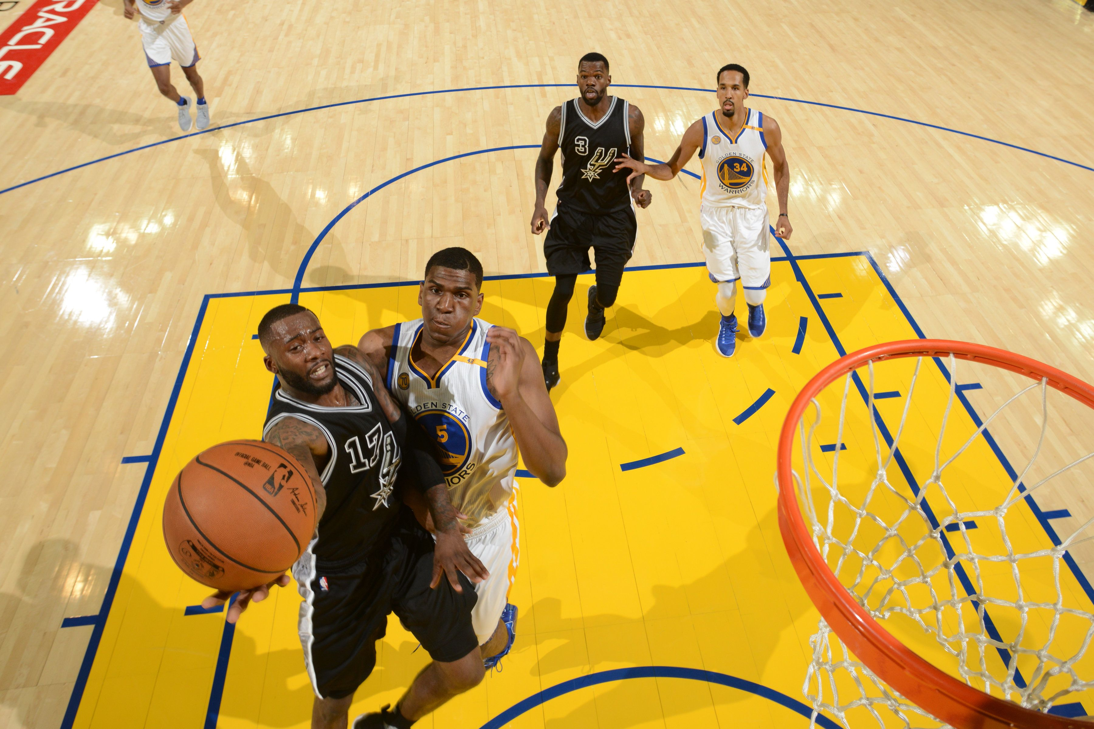 OAKLAND, CA - OCTOBER 25:  Jonathon Simmons #17 of the San Antonio Spurs drives to the basket against Kevon Looney #5 of the Golden State Warriors on October 25, 2016 at ORACLE Arena in Oakland, California. NOTE TO USER: User expressly acknowledges and agrees that, by downloading and or using this photograph, user is consenting to the terms and conditions of Getty Images License Agreement. Mandatory Copyright Notice: Copyright 2016 NBAE (Photo by Noah Graham/NBAE via Getty Images)