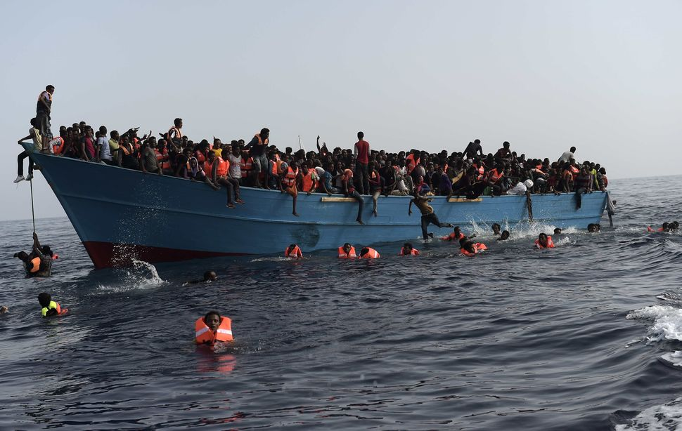 Refugees and migrants wait to be rescued by Proactiva Open Arms NGO in the Mediterranean Sea, some 12 miles north of Lib
