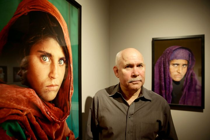 "U.S. photographer Steve McCurry beside his famous ""Afghan Girl"" portrait of Sharbat Gula in 2013. It's been compared to"