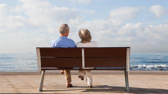 Spain, Mallorca, Senior couple sitting on bench at sea shore
