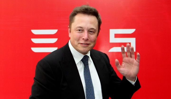 Tesla Motors CEO Elon Musk waves during a news conference to mark the company's delivery of the first batch of electric