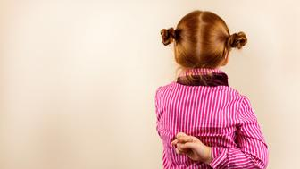 Portrait of cute elegant redhead girl from back with crossed fingers