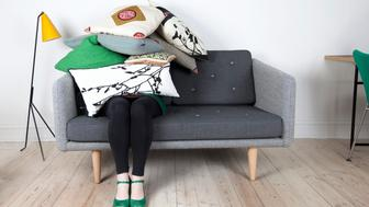 Woman, sitting on sofa, hiding under pile of pillows