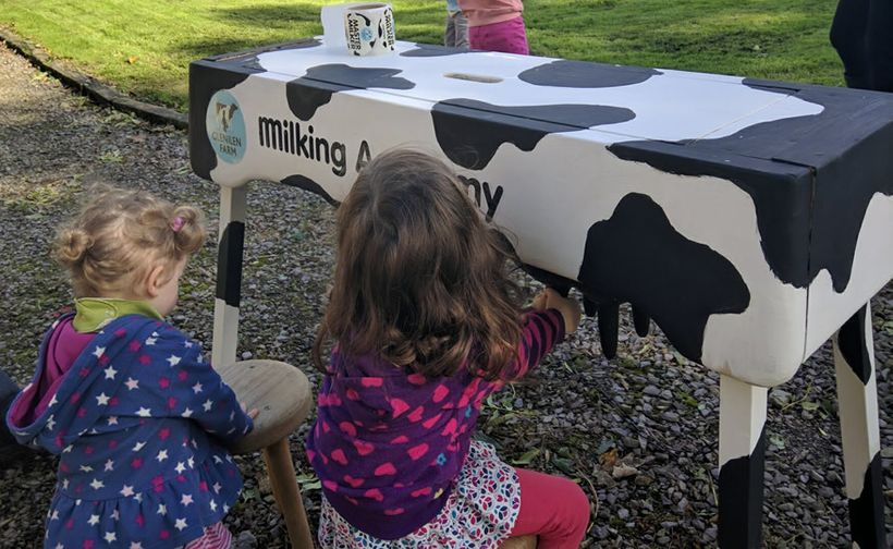 Young guests practice milking
