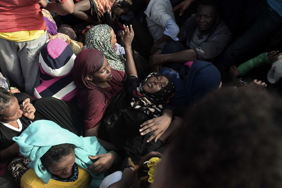 A woman faints while refugees and migrants wait to be rescued in the Mediterranean Sea, some 12 miles north of Libya, on