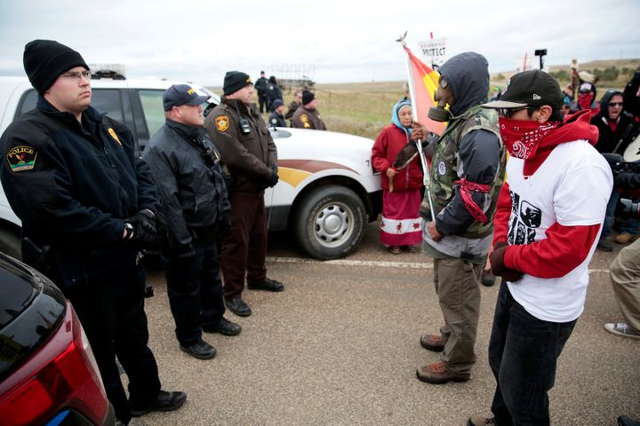 Dakota Access Pipeline protesters square off against police between the Standing Rock Reservation and the pipeline route outs