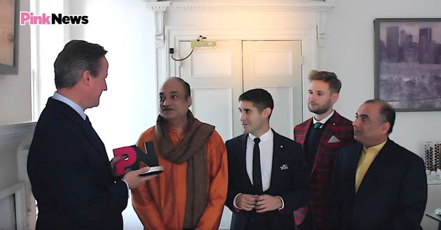 Cameron receiving his 'ally of the year' award from PinkNews executive Benjamin Cohen (second left) with...