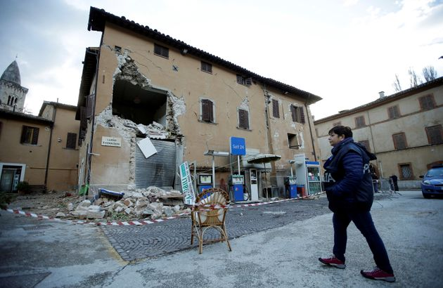 A police officer stands next to a collapsed building after an earthquake in Visso, central Italy on