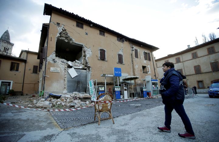 A police officer stands next to a collapsed building after an earthquake in Visso, central Italy.