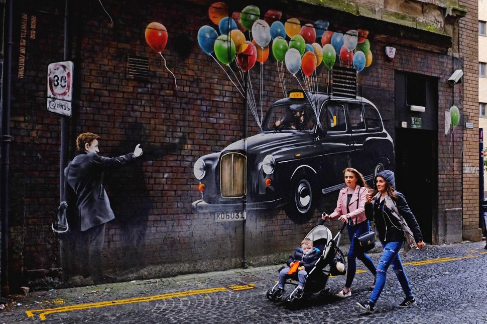 Two woman push a buggy past a mural on Mitchel Lane.