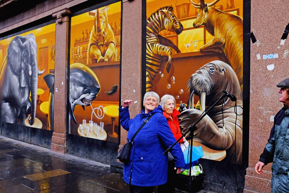 Members of the public walk past a mural on Argyll Street.