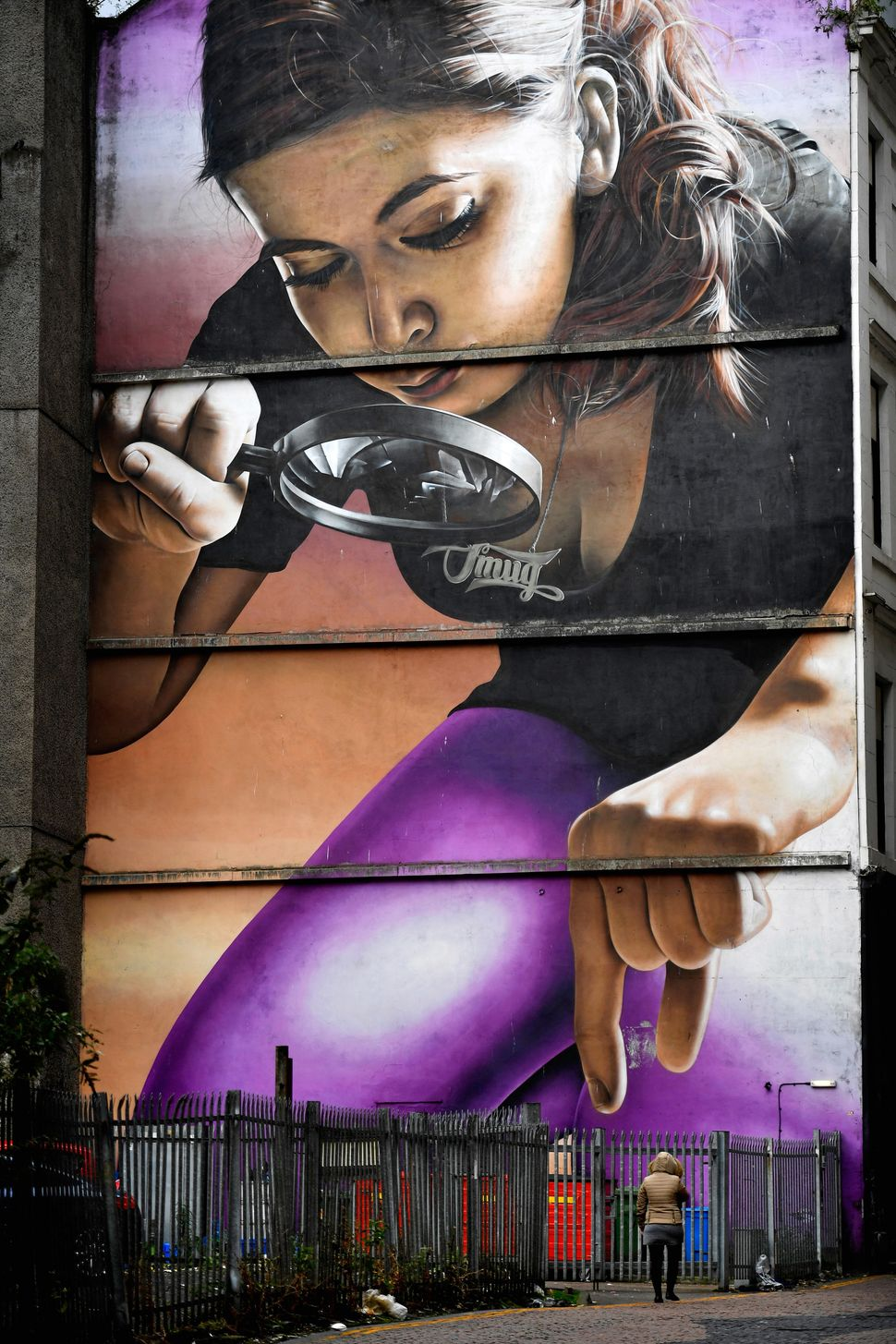 A woman walks past one of the murals on Mitchel Lane.
