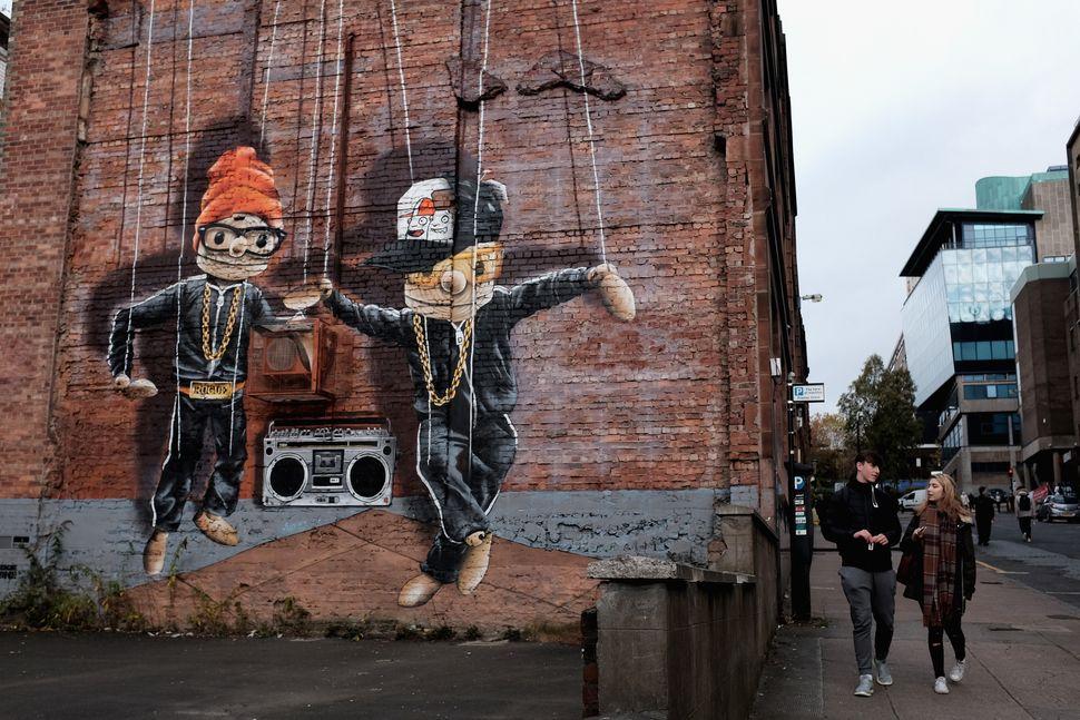 Students walk past a mural onJohn Street.