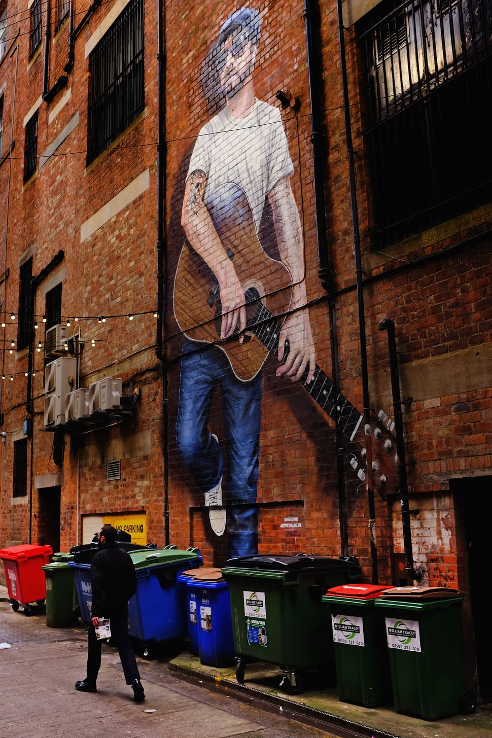 A man walks past a mural on Sauchiehall Street lane.