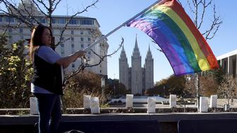 Sandy Newcomb stands with a flag near the Salt Lake Temple after members of The Church of Jesus Christ of Latter-day Saints mailed their membership resignation to the church in Salt Lake City, Utah November 14, 2015. The resignations were prompted by the Mormon church policy barring the children of married same-sex couples from receiving baptism. REUTERS/Jim Urquhart