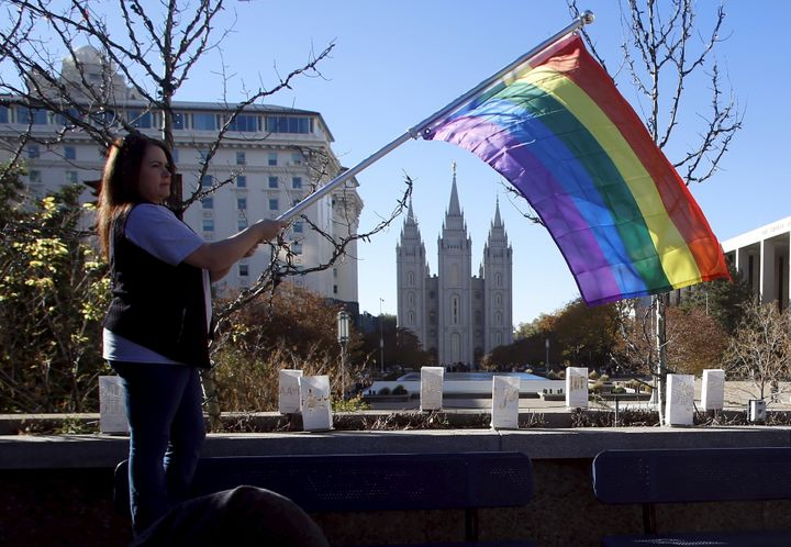 Sandy Newcomb stands with a flag near the Salt Lake Temple after members of The Church of Jesus Christ of Latter-day Saints m
