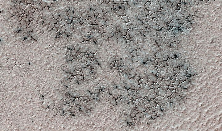 The image shows spidery channels eroded into the Martian ground. It's an example from high resolution observation of more tha