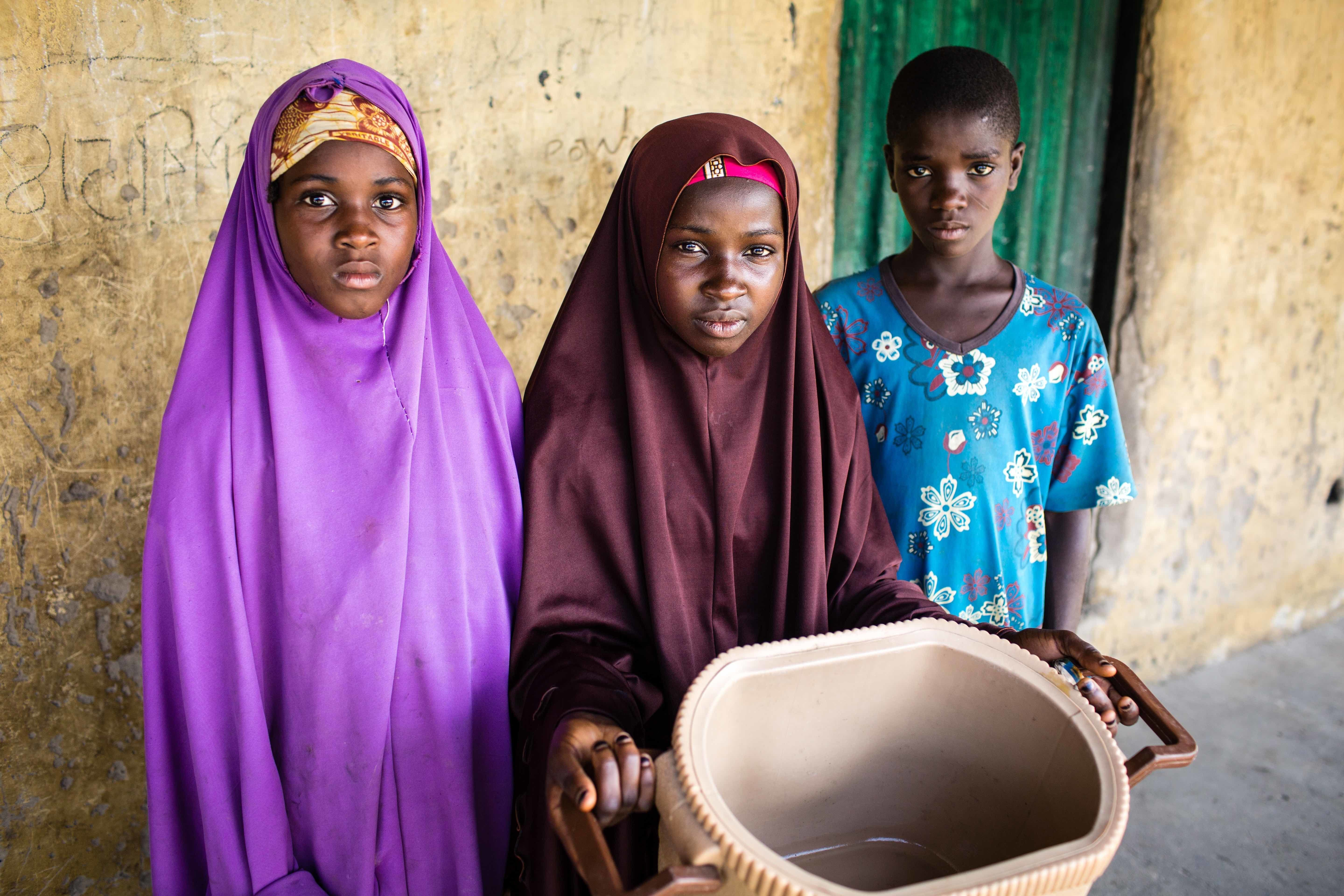 Zulyatu (center), 16, and her younger siblings rarely have enough to eat. Their father died during a Boko Haram raid and thei