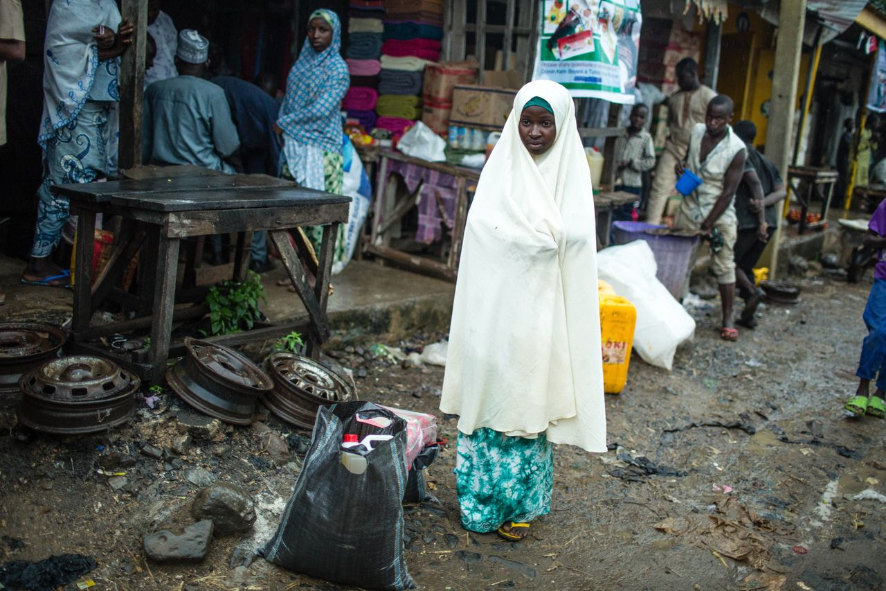 Zulyatu,16, in the market with two bags of food she bought using her e-voucher card. She says there is enough rice in the bag to feed her and her younger siblings for the month.