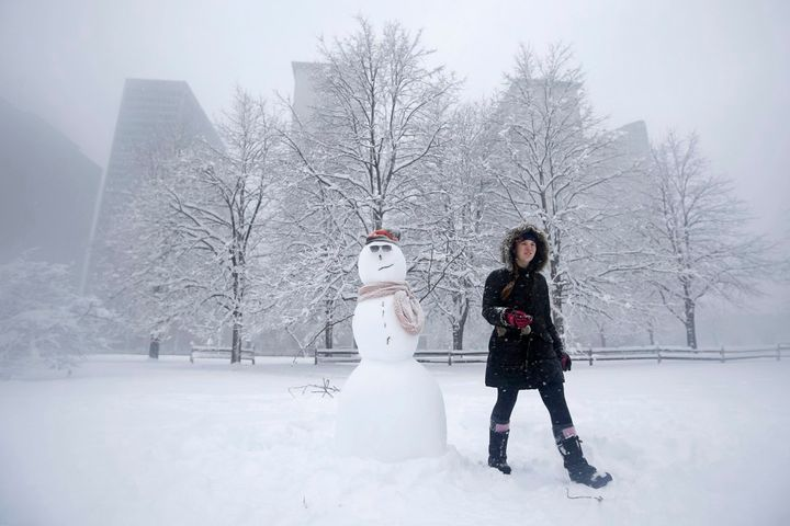 <p>MacKenzie Perkins walks past a snowman she built in a park during blizzard conditions in Chicago, in 2015.</p>