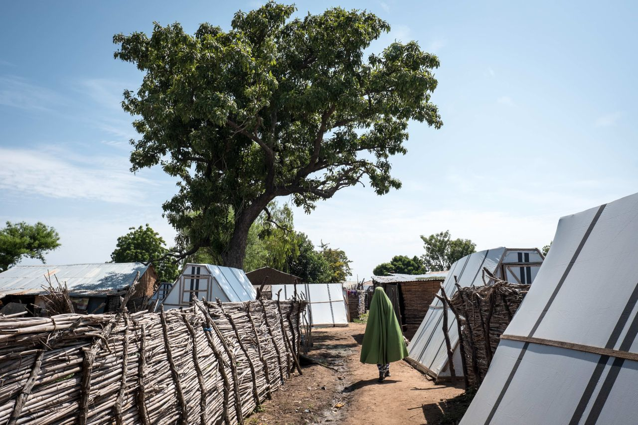 In Sabon Gari, a Nigerian woman displaced by Boko Haram walks in front of her tent.