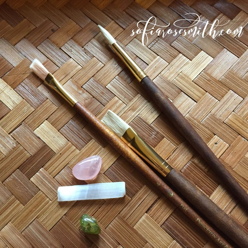 three wooden paint brushes lay atop a bamboo tray. a few stones sit beside them: rose quartz, selenite, and peridot. the text