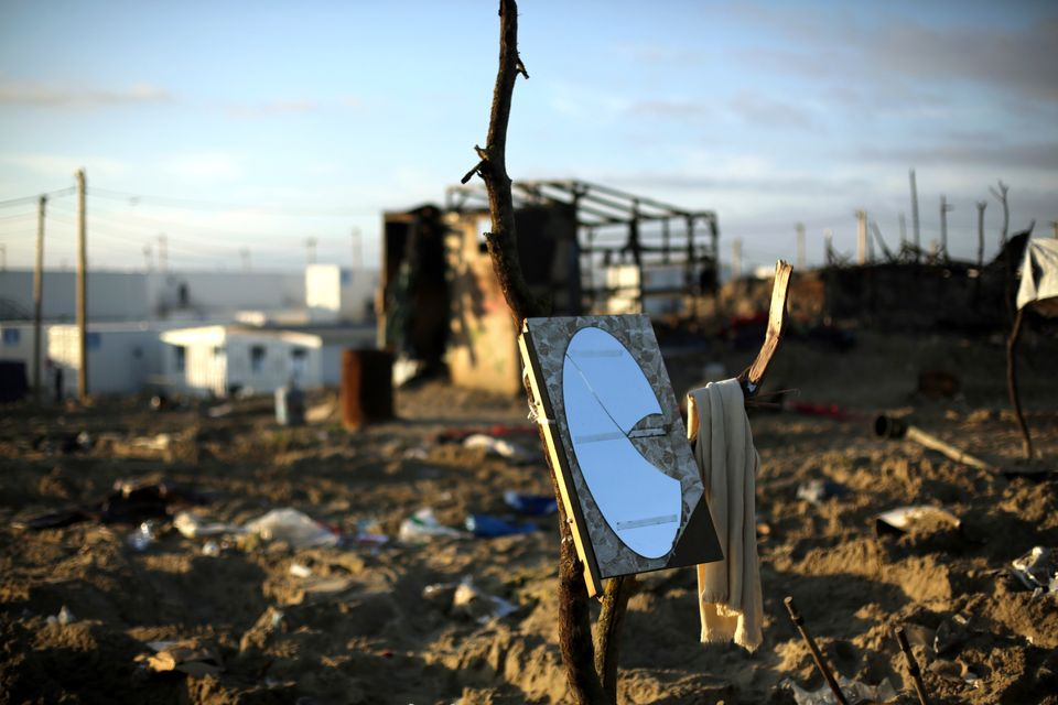 A mirror and a towel are hanging on a branch in the makeshift migrant