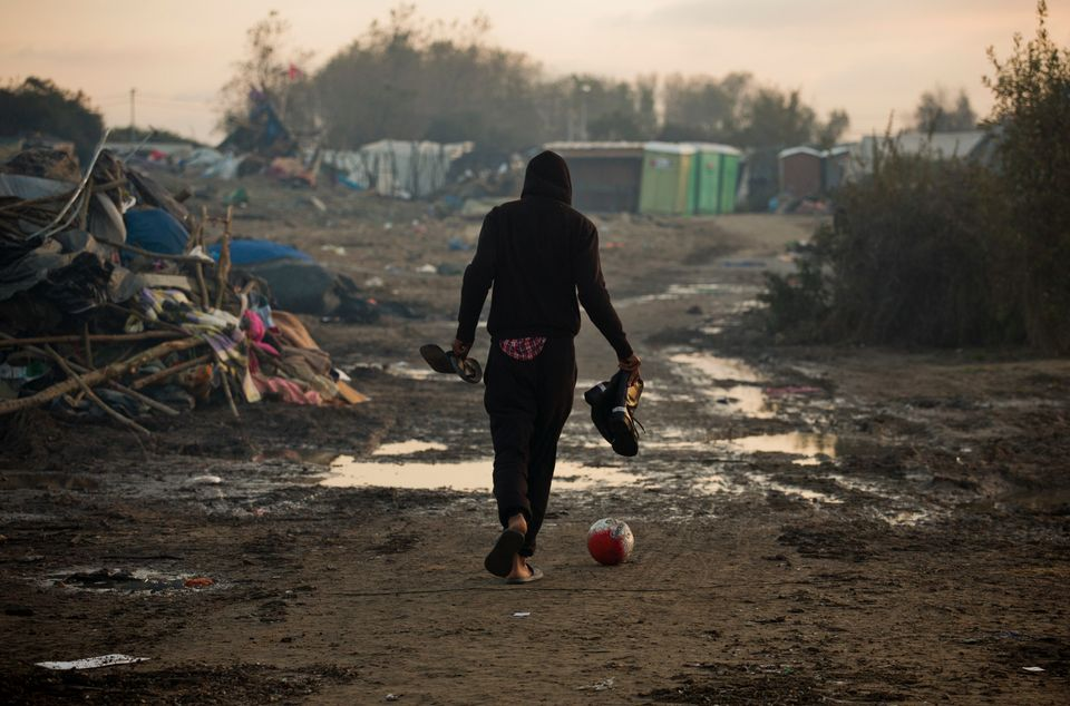 A mankicks a ball as he past tents destroyed in the makeshift migrant