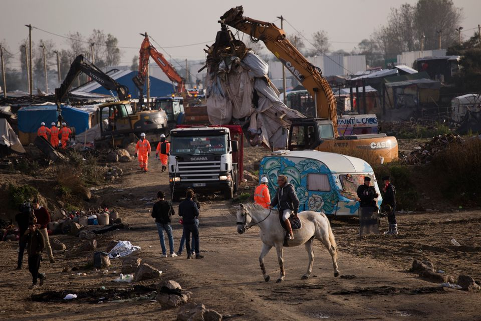 A man rides a horse past mechanical diggers working to clean up a makeshift migrant