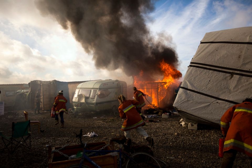 Workers trying to extinguish a tent