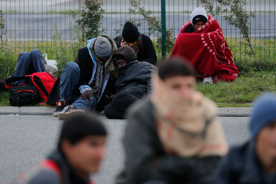 Migrants who say they areminors, use blankets to protect themselves from the cold as they prepare...