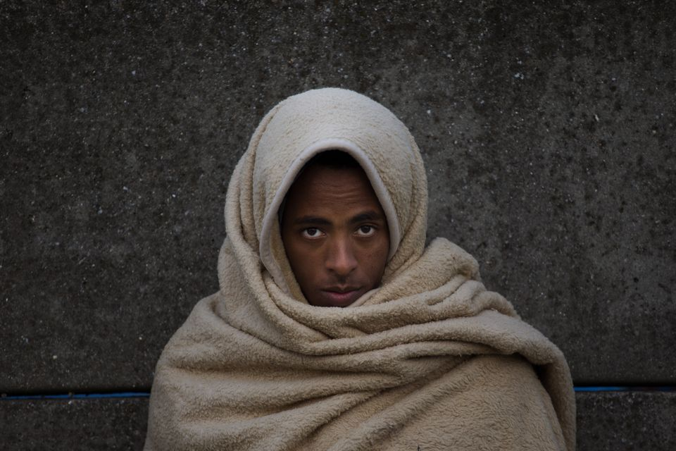 Abdelhamid, 17, from Eritrea, waits with a group of other migrants with nowhere to go, in the hope an...