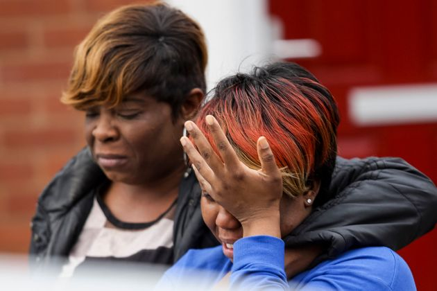 A woman cries as she talks to a police officer at the scene of a house fire in Birmingham that claimed...