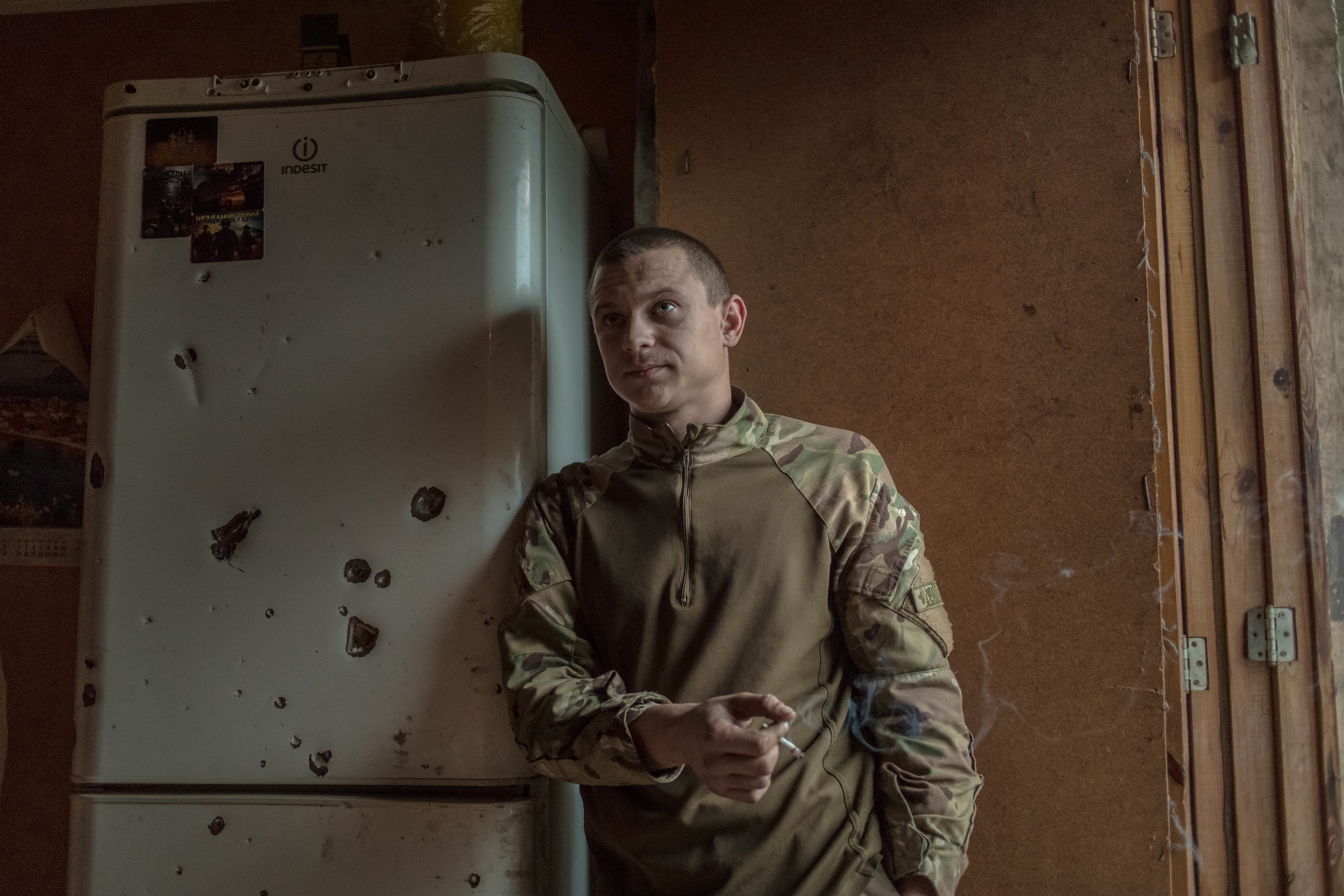A volunteer soldier stands next to a bullet-ridden fridge. He says he joined the unit because he just wanted to fight.