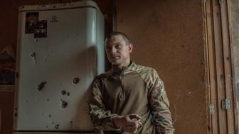 A volunteer soldier stands next to a bullet ridden fridge Hes been given the nom de guerre Chikatilo after Andrei Romanovich Chikatilo a Soviet serial killer nicknamed the Butcher of Rostov He earned his nickname because he rarely speaks but when he does he stares through you with a deep cold stare Chikatilo was a taxi driver before he joined the war and says he joined just because he just wanted to fight Although he respects the other members of the unit he says the only one he fully trusts is Shorok whom hes been friends with since childhood