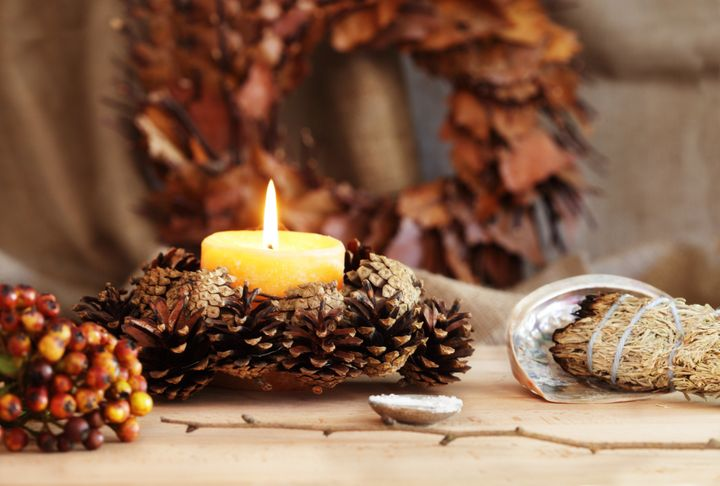 A pagan altar is decorated for Samhain. Altar items include a sage smudge stick resting in an abalone shell, a hazel wand, a