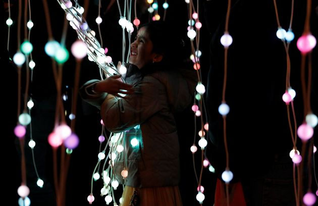 A girl plays in the ocean of lights attraction during the Diwali lights switch on in Leicester, Britain...