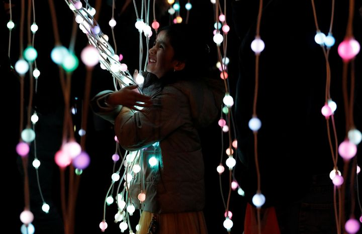 A girl plays in the ocean of lights attraction during the Diwali lights switch on in Leicester, Britain October 16, 2016.