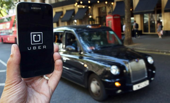 The Uber logo is seen on a smartphone while a British taxi waits in the background in this 2016 file photo.